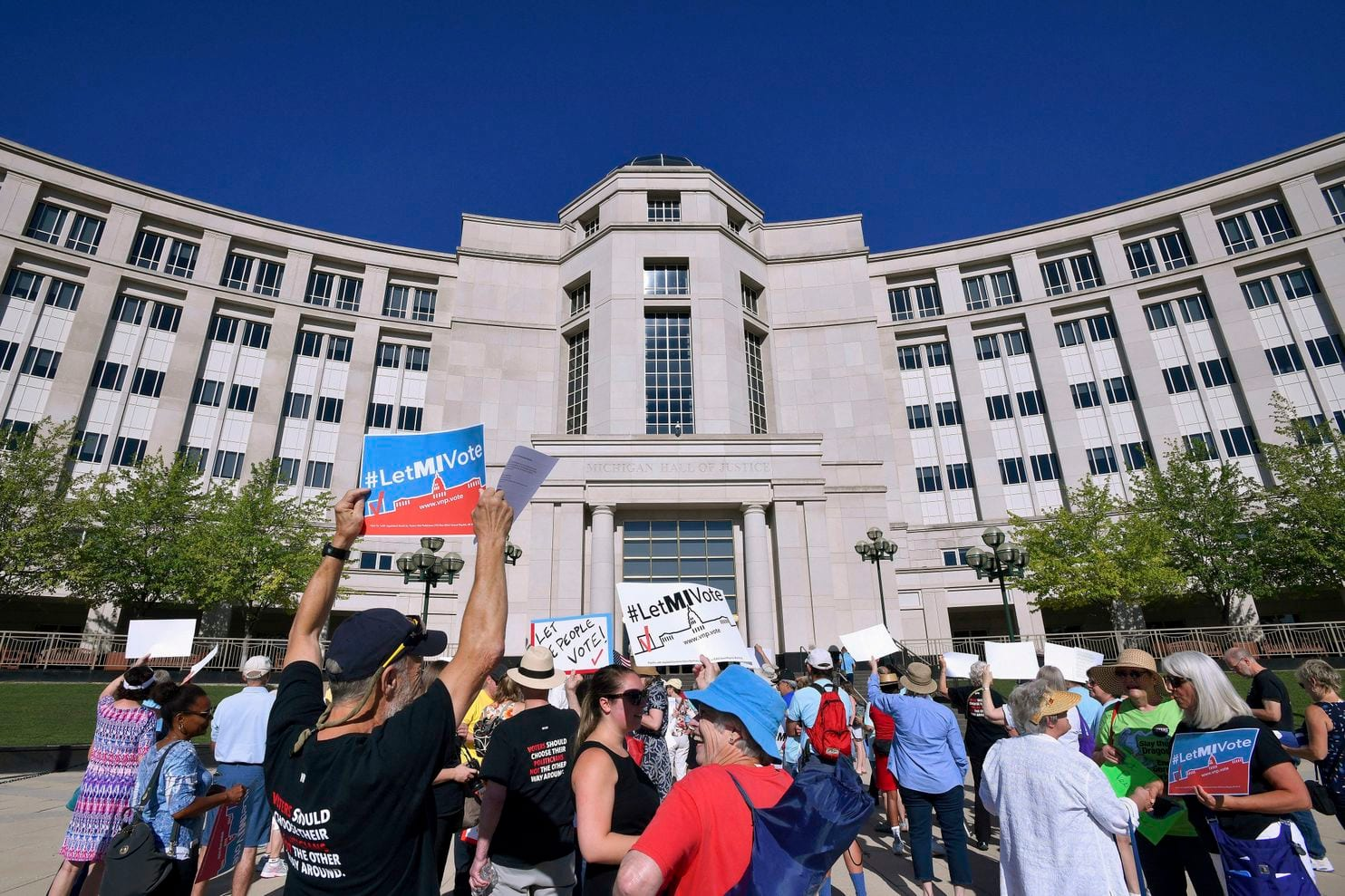 Demonstrators rally outside the Michigan Hall of Justice in Lansing, Mich., where the state's Supreme Court heard arguments in July about whether voters in November would be able to pass a constitutional amendment that would change how the state's voting