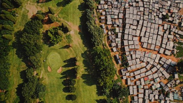 A sprawling informal settlement sits near the manicured fairways of a golf course in Durban, South Africa. The wealth of billionaires has increased by $900 billion in the last year. Meanwhile, the poorest half of the world saw its wealth decline by 11%