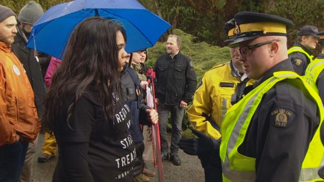 An anti-pipeline protester at a Kinder Morgan terminal in Burnaby speaks with a RCMP officer on Saturday, March 24, 2018. (CBC)
